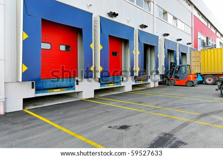 Forklift at cargo dock of big warehouse