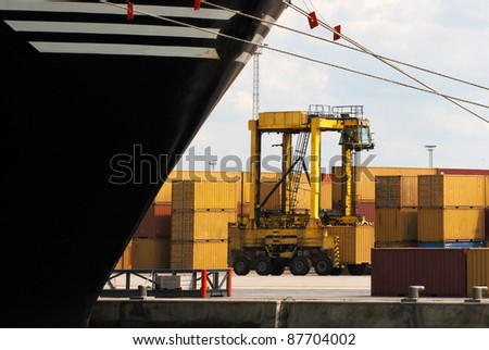 Forklift carrying one single container near a huge container ship (carrying more than 3000) in Antwerp world harbor