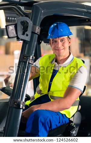 forklift driver in protective vest and forklift at warehouse of freight forwarding company, smiling