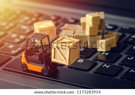 forklift freight car truck loading goods product wooden boxes and parcel on laptop computer keyboard ecommerce logistic warehouse industry concept