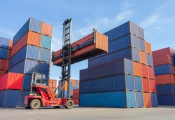 Forklift handling container box loading to truck in shipping yard with cargo container background, Logistic industrial concept.