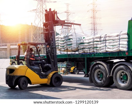 Forklift handling white sugar bags from warehouse for stuffing into a truck outdoors.
