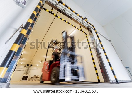 Forklift in a large industrial freezer warehouse. Empty warehouse for vegetable storage. Background