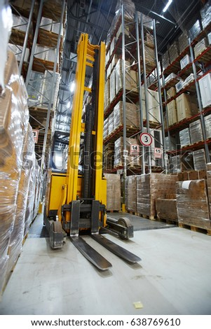 Forklift in aisle of large-scale warehouse #638769610