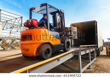 Forklift is putting cargo from warehouse to truck outdoors #651404722