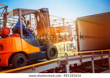 Forklift is putting cargo from warehouse to truck outdoors at sunny sky background. #481182616