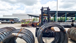 Forklift is working by lifting the wire rod coil and move to another place in wire factory
