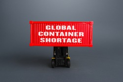 Forklift lifts the container with the inscription Global container shortage. Logistics problems due to world economy lockdowns. Limiting the volume of exports and increasing cost of transporting goods