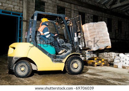 forklift loader at warehouse indoors stacking cement packs to stockpiles