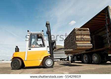 Forklift loader for warehouse works outdoors loading (unloading) a long lorry truck - stock photo
