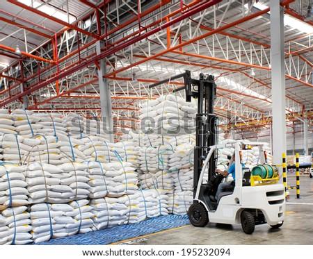 Forklift loader with big bag of sugar in distribution warehouse