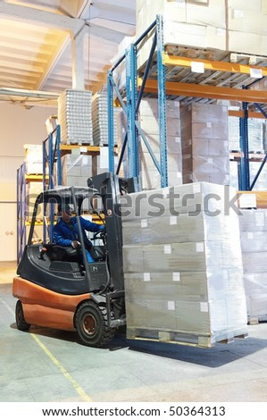 Forklift loader with worker driver at warehouse moving a cardboard boxes - stock photo