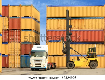forklift loading containers on white truck in harbor