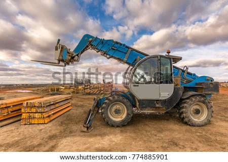 Forklift on a construction site, preparing to raise construction parts