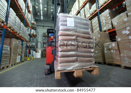 Forklift operator in red uniform and blue helmet at work in warehouse