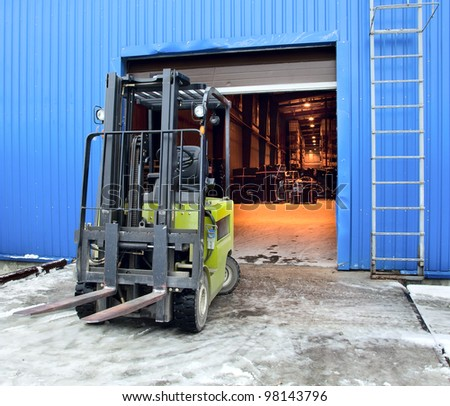 Forklift standing at the entrance of a large modern warehouse