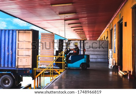 Forklift stuffing-unstuffing pallets of cargo to container on warehouse leveler dock. Сток-фото ©