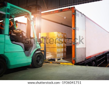 Forklift Tractor Loading Package Boxes into Cargo Container. TrailerTruck Parked Loading at Dock Warehouse. Shipment Delivery. Supply Chain. Shipping Warehouse Logistics. Freight Truck Transport Stockfoto ©
