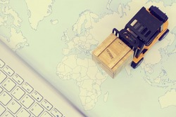 Forklift truck handing cargo shipping container box with keyboard and worldmap background use as international, oversea and worldwide logistic, shipping, import and export concept.