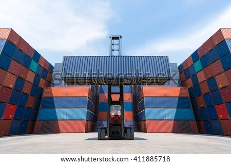 Forklift truck lifting cargo container in shipping yard for import,export, logistic industrial with container stack background