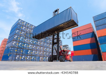 Forklift truck lifting cargo container in shipping yard or dock yard with cargo container stack in background for transportation import,export and logistic industrial concept