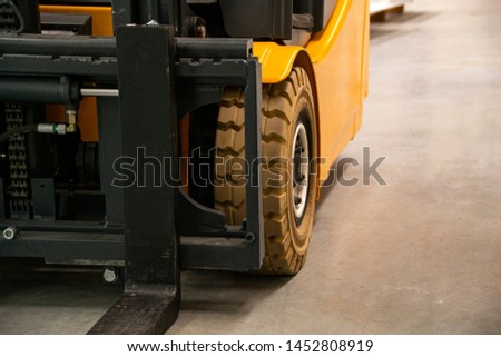 Forklift Truck. Wheels. Close view of Yellow Black Fork hoist . Eletric counterbalance carriage. Warehouse equipment.