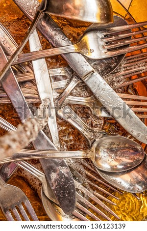 Forks, spoons, knives and  dishware washed under a stream of water