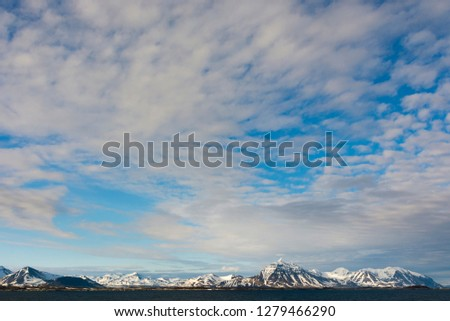 Forlandsundet. Snowy mountains and cirrus clouds under the midnight sun.