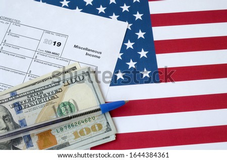 Form 1099-misc Miscellaneous income and blue pen with dollar bills lies on United States flag. Internal revenue service tax form Stock foto ©