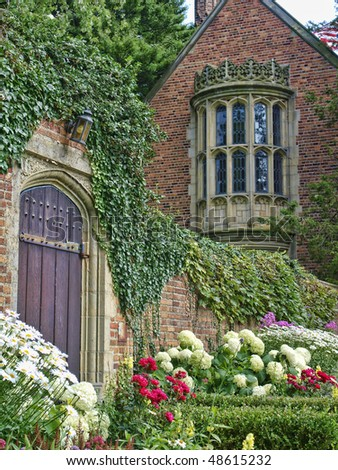 Formal brick home with gorgeous stained windows surrounded by a brick wall with an old garden gate. The summer garden is in full bloom.