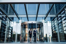 Formal contemporary man and woman talking while walking out of round revolving doors of modern glass building of corporation office