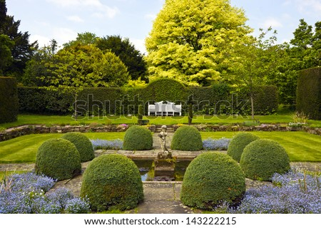 Formal garden with white wooden bench and topiary shrubs.