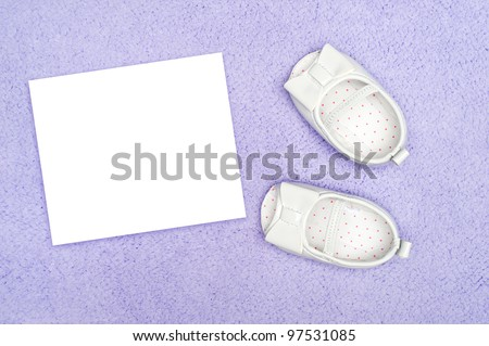 Formal infant dress shoes on purple carpet with blank, white card for copy