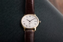 Formal wristwatch with white dial, gold case, brown leather strap with crocodile skin patterns on textured leather background.