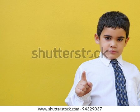 Formally dressed latin boy on a yellow wall with space for text