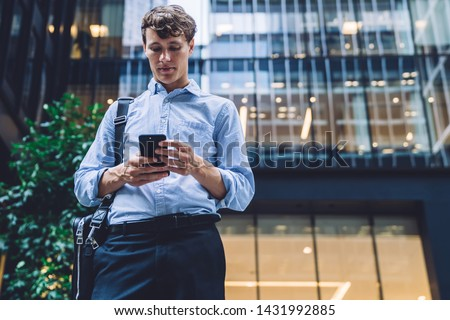 Formally dressed male executive manager in trendy clothes using mobile phone outdoors, Caucasian businessman sending text messages via smartphone connected to 4G internet for online chatting