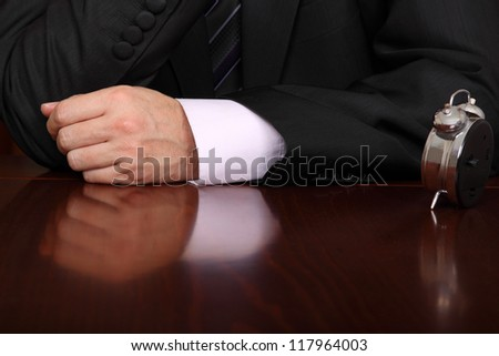 formally dressed man at a desk with a clock on it