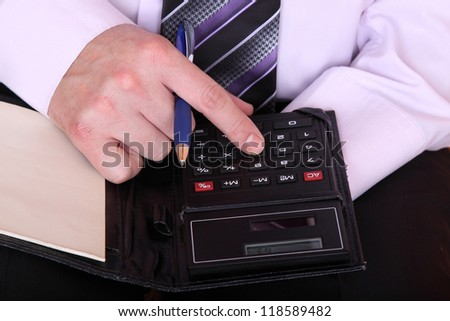 formally dressed man using the calculator closeup