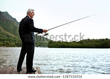 Formally dressed mature businessman fishing on the lake. #1287510316
