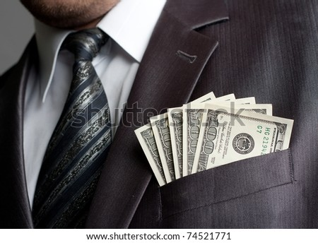 Formalweare businessman with earned money in suit pocket
