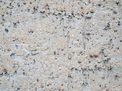 Format-filling view of a roughly plastered gray wall with coarse pebbles.