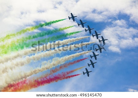 Formation of nine aerobatic aircrafts during airshow of aerobatics. Colored smoke behind planes. Exhibition of pilotage and maneuvering skills