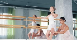 Former ballerina trainer helps girl dancer do exercises for legs leaning on wooden barre at mirror in ballet studio