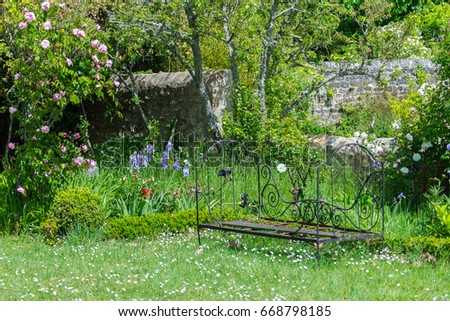 Former bench in a bloom french garden, nice decoration #668798185