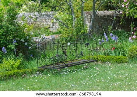 Former bench in a bloom french garden, nice decoration #668798194