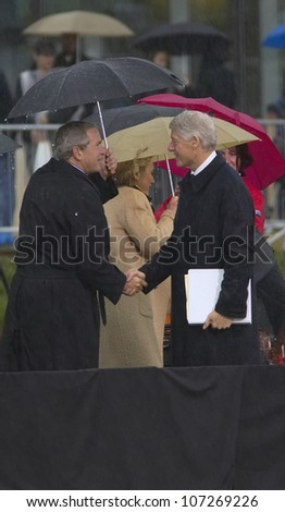 Former US President Bill Clinton shakes hands with US President George W. Bush during the grand opening ceremony of the William J. Clinton Presidential Center in Little Rock, AK 18 November 2004.