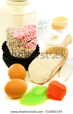Forms for baking cakes and scoop of flour on a white background.