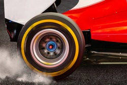 Formula rear wheel spinning and drifting after launch on a dark asphalt race track