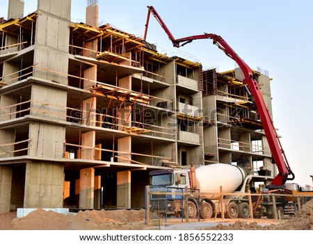 Photo of  Formworks and pouring concrete through a сoncrete pump truck connected to a ready-mixed truck. Concrete line and boom pumping at construction site. Tower cranes construct residential building