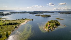 Fornebu beach in Oslo, Norway with fjords in the background and boats on the sea
